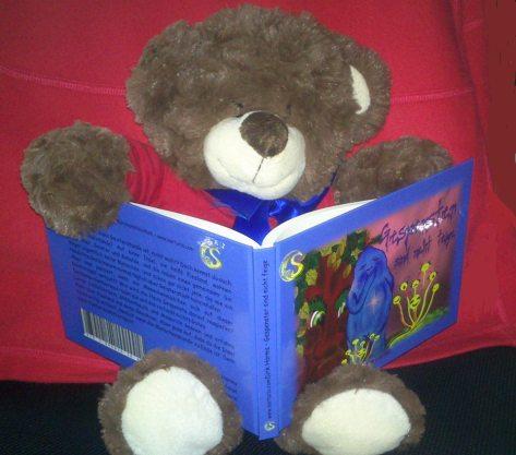 """Maskottchen Teddy Valentin liest """"Gespenster sind nicht feige""""."""